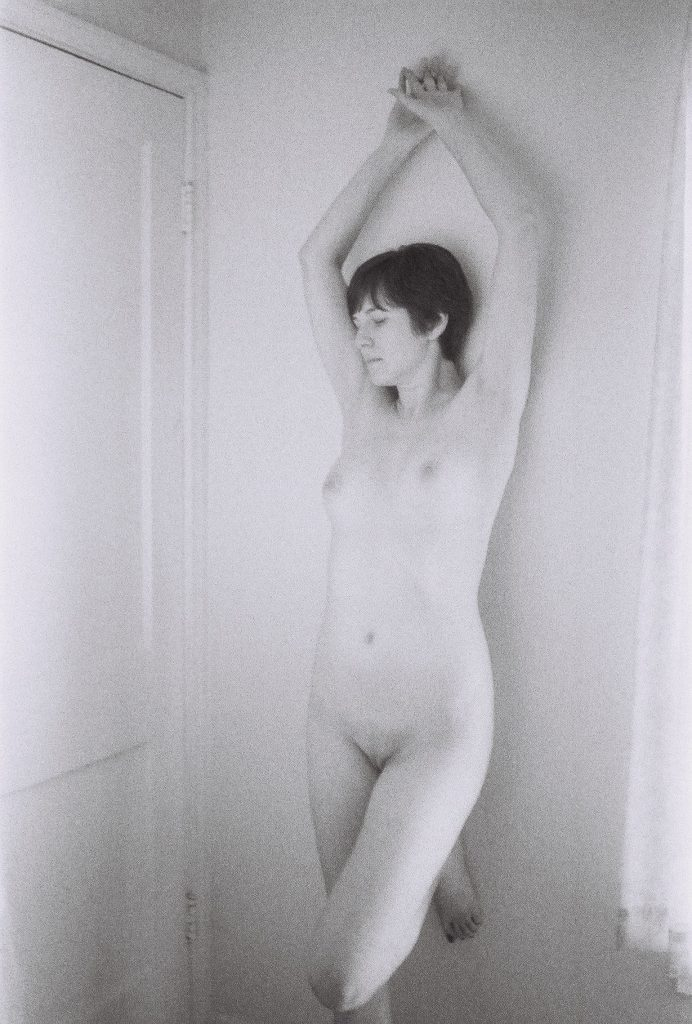 Black & White image, female model, hands crossed over head, looking door.