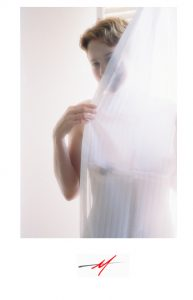 Color image, female model nude, peeking out from curtain.