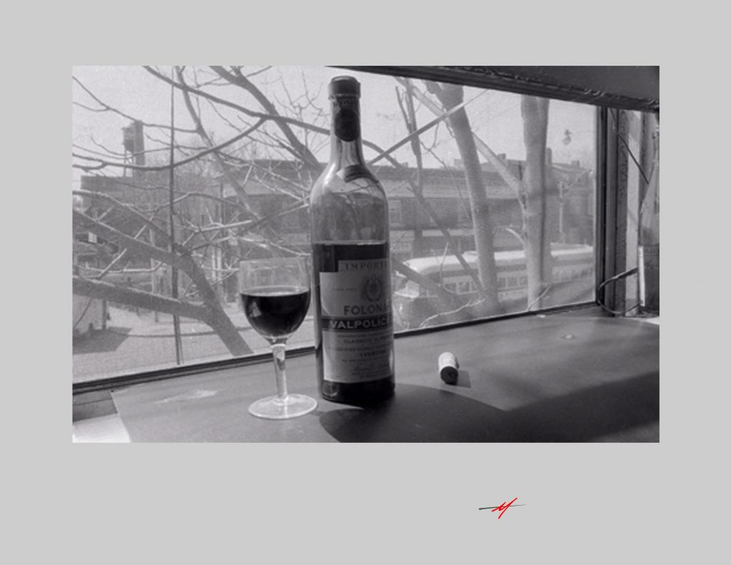 """Black and White image, 1970""""s view wine bottle and cork, old streetcar in back."""