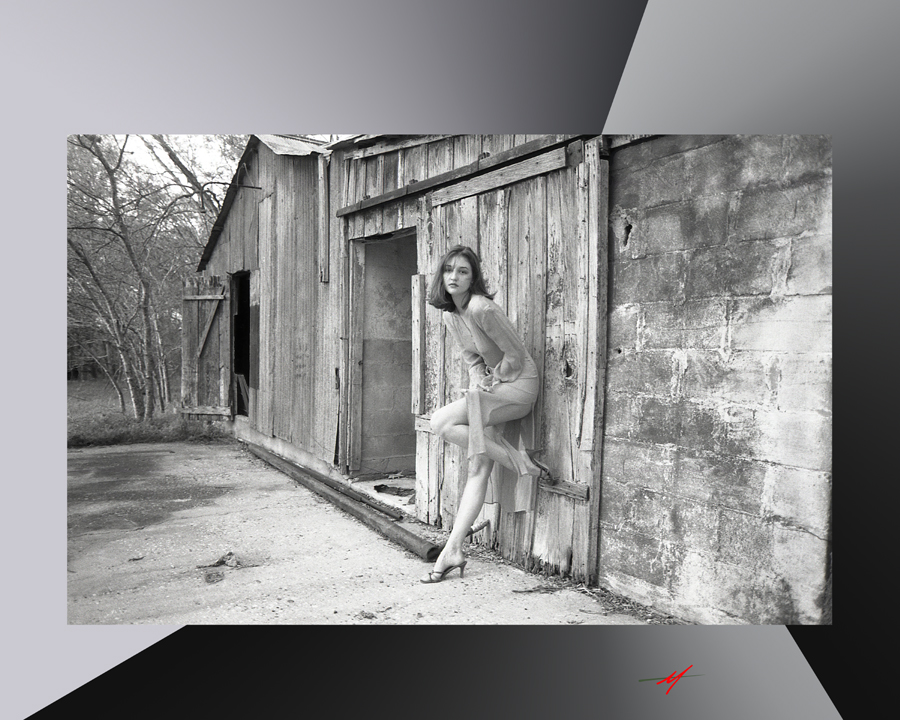 Black and white image, red haired female model transparent dress, front of an milk barn.