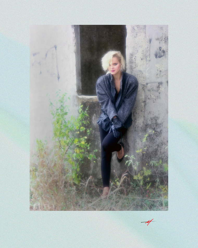Color image, cute blond, winter wear, standing in front of a silo, last of winter greenery.