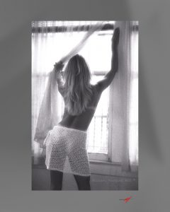 Black & White image, topless, long haired blond, in front of bedroom window, staring out window, wearing a white sarong.