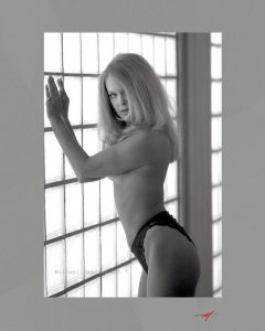 Black & white image, glass block wall, topless,black panties, blond leaning against wall.