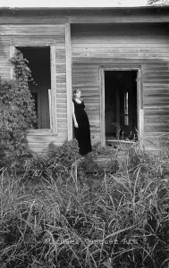 Black and White image, old house overgrown with vegetation, shot in the late 60's.