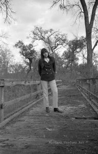 Late 60's black haired beauty on a golf bridge over creek.