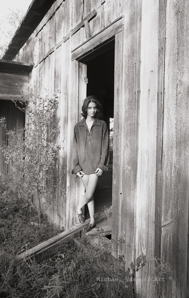 Black and white image, young dark haired model, wearing a shirt, overgrown weeds.