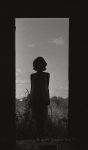 Black and white image, silhouette of a woman, abandon house, overgrown weeds and sky.