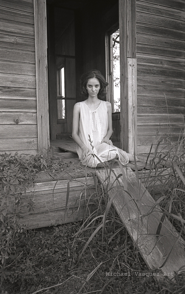 Young, dark haired, night gown, old house in the countryside, overgrown weeds.