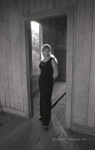 Black and White image,full length shot of a young Caucasian woman wearing a grown.